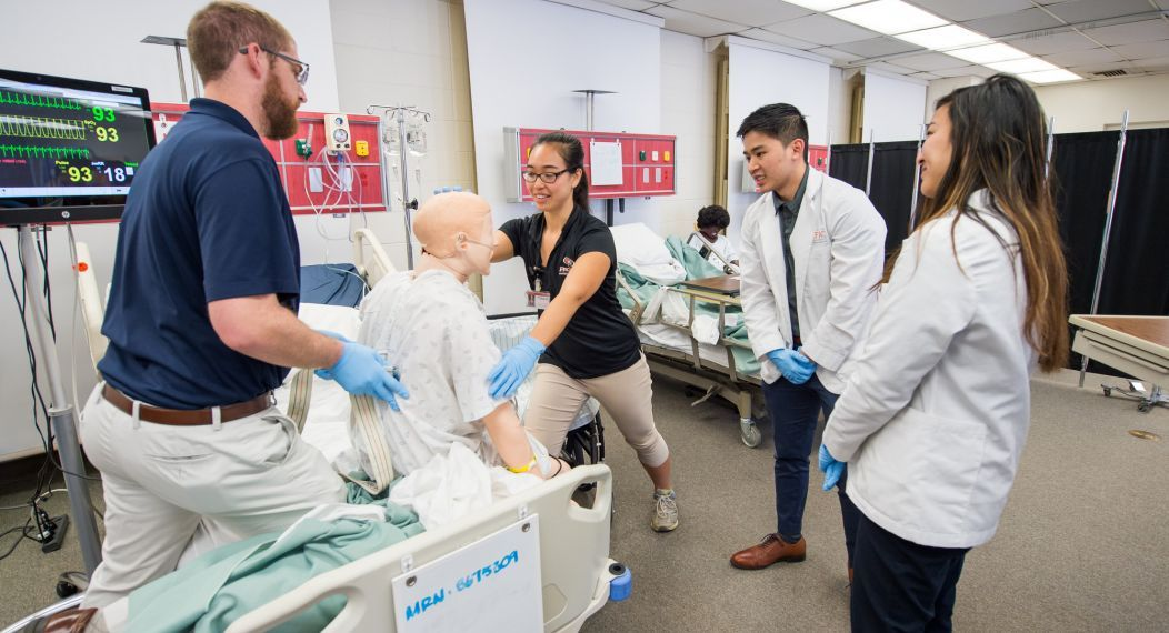 Physical therapy, pharmacy and speech language pathology students run through patient case studies in the simulation lab as part of an interprofessional education program